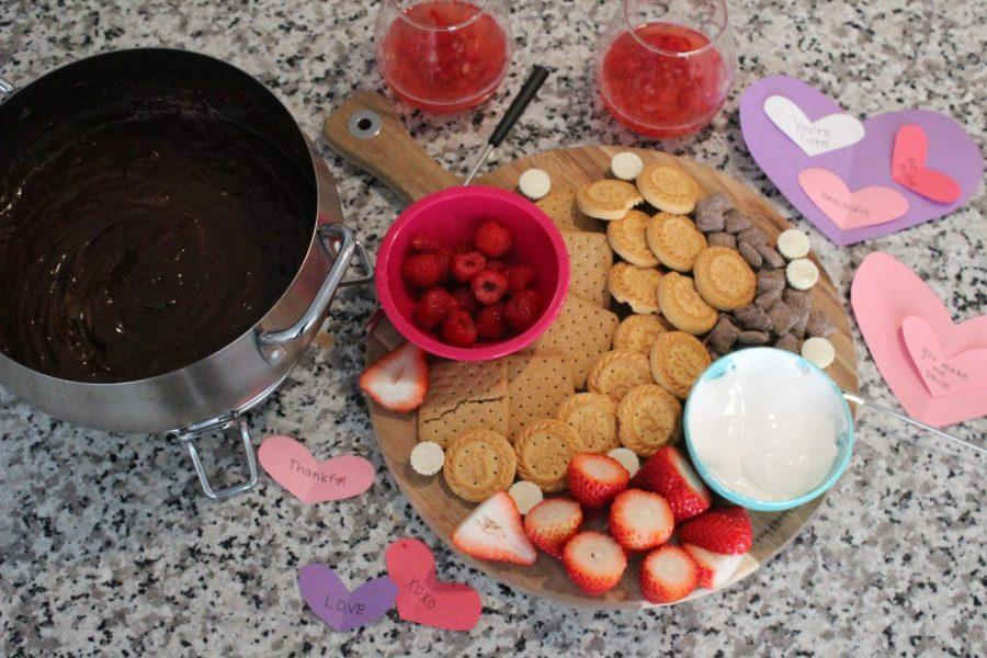 In this photo you see a charcuterie board and heart shaped cutouts dedicated to valentines day sweets and treats. Valentines day is coming up and if you are spending it with friends, family, or significant other, there is always room to eat and make a small craft!