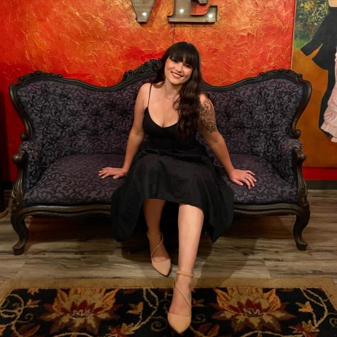 """Editor-in-Chief Jaycee Kalama sits on a velvet couch and a sign that reads """"Love"""" hangs above it. Jaycee has long, curly hair with bangs that cover her forehead. She is wearing a long dress and heals."""